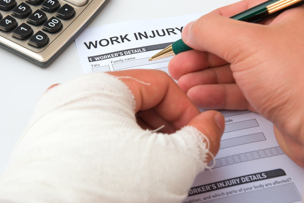 man filling out a claim after an injury at work